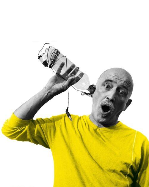 André Mainvielle, l'air étoné, approchant une bouteille de son oreille
