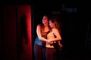 Deux femme de profil se prennent dans les bras et semblent parler joyeusement à un troisième interlocuteur hors champ